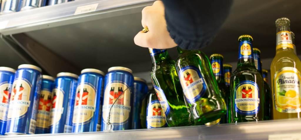 Jugendschutz Hand nimmt bei einem Alkoholtestkauf ein Bier aus einem Verkaufsregal