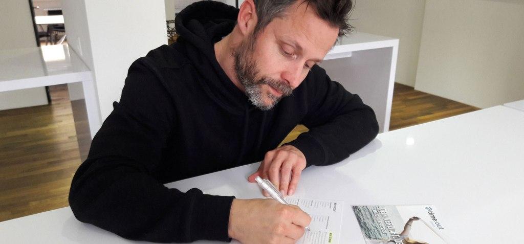 Radiomoderator Simon Mosers füllt auf einem weissen Tisch seine time:out-Anmeldung aus